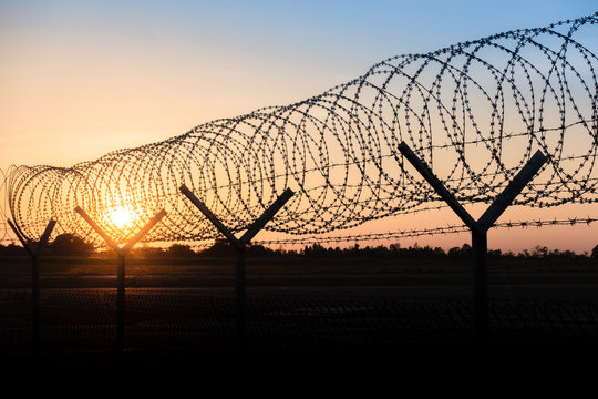 Silhouette of a barbed wire fence steel jail  with the sunset in the background