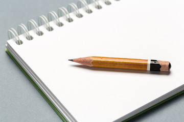 Short worn pencil with notepad on gray desk