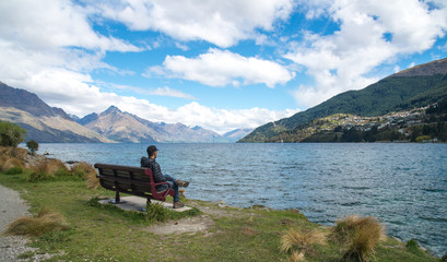 Man sitting on the chair near the waterfront of lake Wakatipu in Queenstown, New Zealand.
