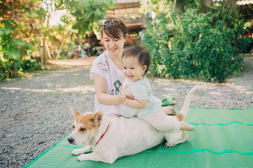 Mother try to let her baby play and riding a dog.Some research reveal that children who live with pet appeared to have greater social skills and be the happiness people.