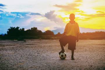 Silhouette picture of kid playing soccer football for exercise under the sunlight.