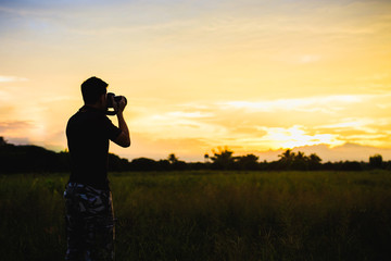 Photographer takes a photo of sunset landscape in the rice field. Silhouette picture style.