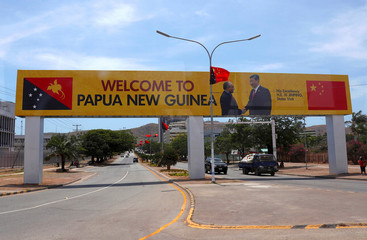 A banner displaying a photograph of Chinese President Xi Jinping shaking hands with Papua New Guinea's Prime Minister Peter O'Neill is seen over a main road in central Port Moresby