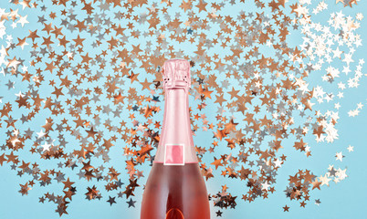 Creative photo of champagne bottle with confetti on blue background