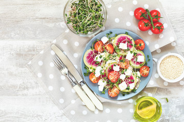 Healthy delicious tasty salad with tomatoes, radishes, cheeses, sprouts and sesame in plate