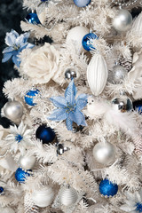 White Christmas tree with blue toys.