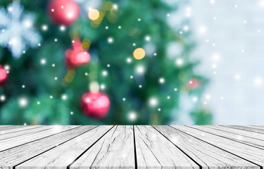 abstract blurry beautiful of decoration Christmas tree with blink snowfall background and plank wooden texture floor for show,advertise,promote product concept