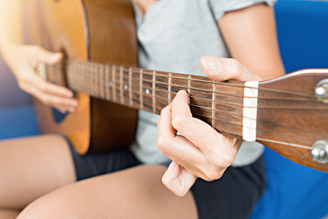Woman playing acoustic guitar.