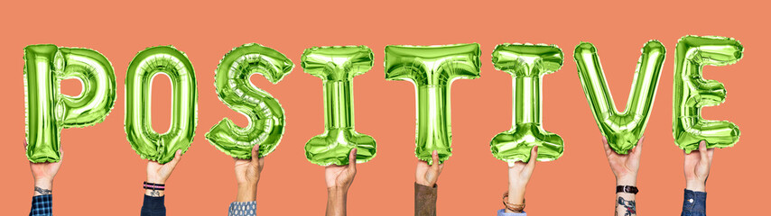 Green alphabet balloons forming the word positive