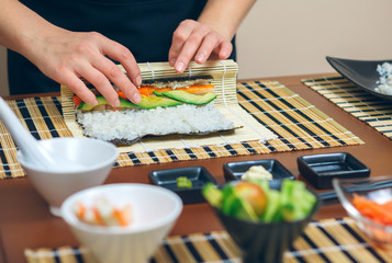 Detail of hands of woman chef rolling up japanese sushi with rice, avocado and prawns on nori seaweed sheet