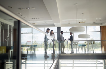 Group of business people walking and taking at stairs in an office Wall mural