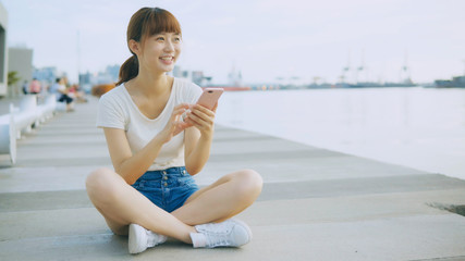 Asian girl using smart phone in the park
