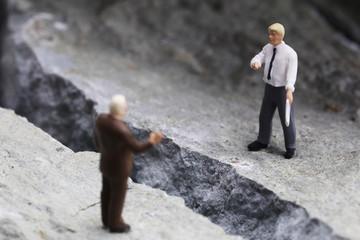 岩の亀裂と交渉するビジネスマンたち