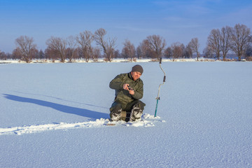 Winter fishing concept. Fisherman in action. Catching fish from snowy ice.