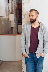 Young man in casual clothing leaning on wall