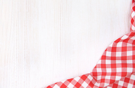 Kitchen red checkered table cloth frame on white wooden empty space background.