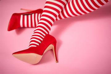 sexy santa woman's legs on a light pink background