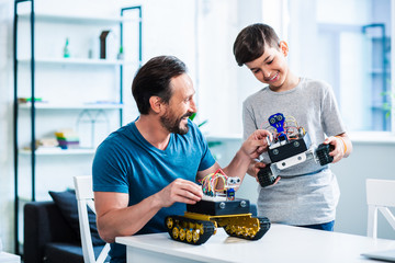Positive adult man constructing his robotic devices
