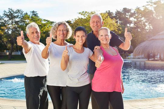 Senioren am Pool mit Daumen nach oben