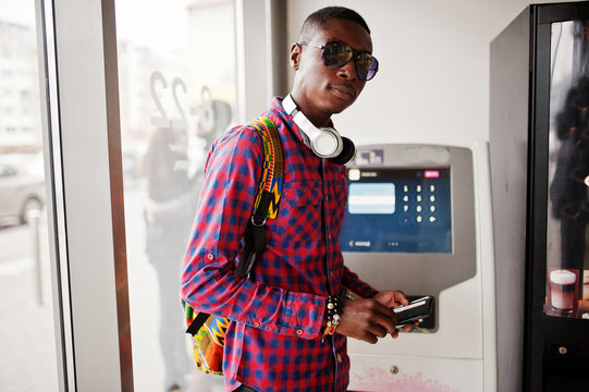 African american man in checkered shirt with backpack holding wallet in hand against atm. Black man traveler.