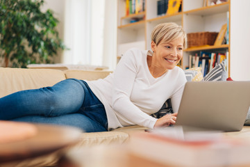 Attractive woman relaxing on a sofa using a laptop