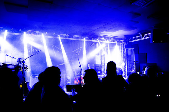 Silhouettes of concert crowd in front of bright stage lights, small pub with band and people