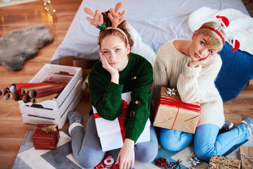 Two bored girls preparing christmas gifts for Christmas