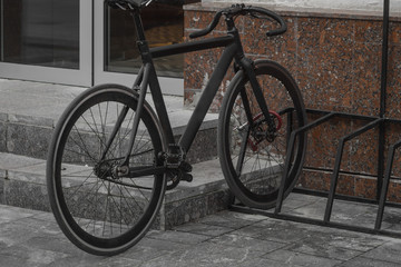 Black sports bike on the fence on a pedestrian street. Autumn day
