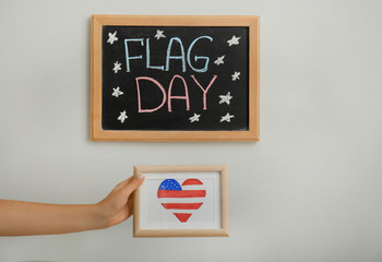 Woman holding picture with heart shaped drawing of American national flag on light background
