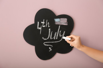 Woman writing on blackboard. 4th July celebration