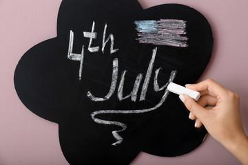 Woman writing on blackboard. 4th July celebration