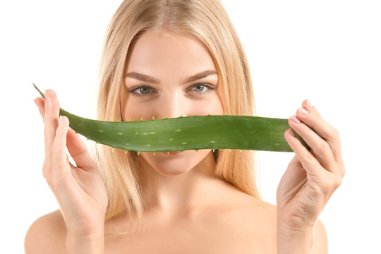 Beautiful young woman with aloe vera on white background