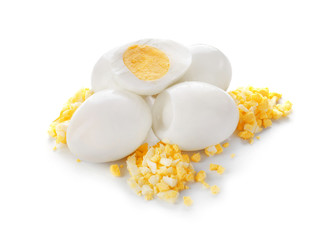 Whole and cut boiled eggs on white background