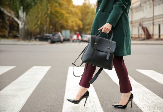 Beautiful fashionable woman crossing road