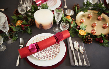 Close up of Christmas table setting with Christmas crackers arranged on plates, elevated view