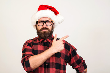 Handsome bearded man in Santa hat and glasses. Santa man pointing to the side over white wall. Christmas concept. Mock up, copy space for text. Hipster bearded man thinking for christmas gift ideas.