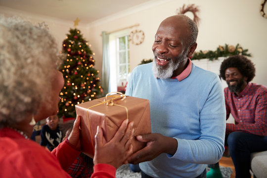 Senior Couple Exchanging Gifts As They Celebrate Christmas At Home With Family