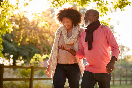 Senior Father With Adult Daughter Enjoying Autumn Walk In Countryside Together