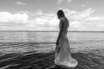 Sad and grieving bride drowning on the lake