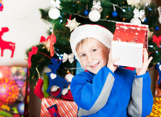 beautiful bright cheerful happy child boy is very happy gift presented for Christmas and New year emotionally surprised and cowardly gift near the ear listening to what's inside