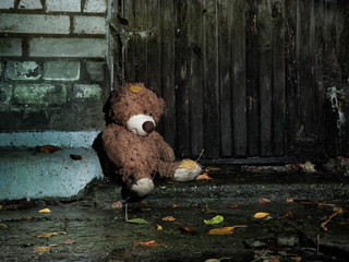 Sad wet plush bear on the background of textured old wooden wall