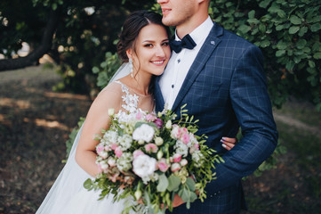 Beautiful newlyweds cuddle in a green garden with trees. Young bride and cute bride with a bouquet are standing in the park. Wedding photography. Stylish portrait.