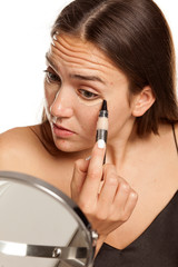 young beautiful girl applying concealer under her eyes on white background
