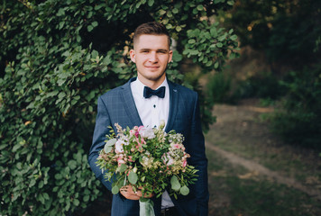 A young and stylish groom stands on the background of nature with green foliage, with a bouquet in his hands. Wedding portrait. Family photo.