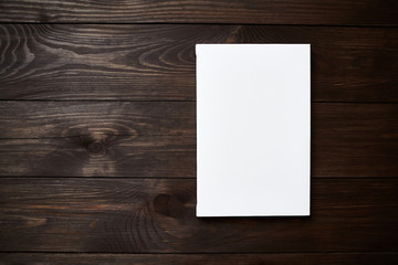 White blank canvas on brown wooden background with copy space. Mockup. Front view