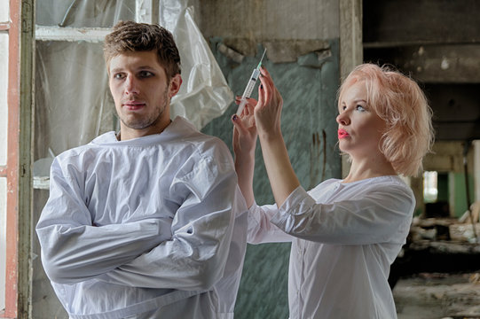Asylum nurse or doctor with a syringe in hand is preparing to give an injection to an insane psycho patient in a straitjacket