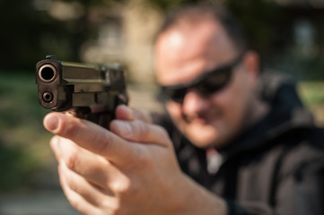 Police agent bodyguard gun pointing pistol to attacker. Front view
