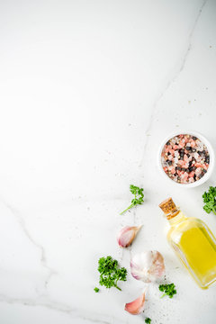 Cooking background with spices, olive oil and herbs, white marble background, copy space top view