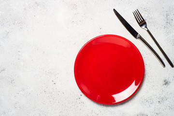 Red plate and cutlery  on light stone table.