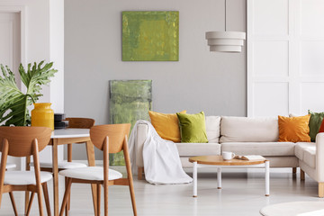 Wooden chairs at table in grey flat interior with pillows on corner couch near green posters. Real photo